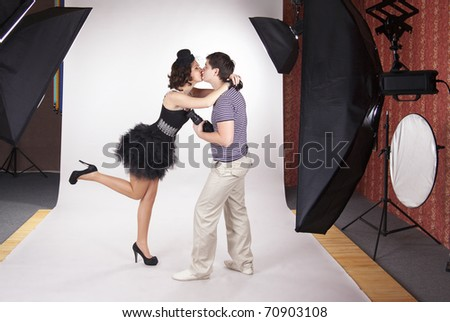 Young model kissing the photographer in the photostudio - stock photo