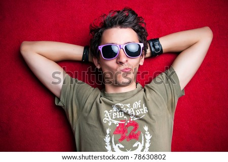 Young model making strange faces on red background, wearing purple sunglasses. isolated - stock photo