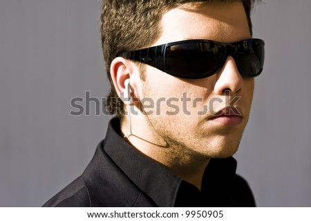 Young model performing security agent isolated on grey - stock photo