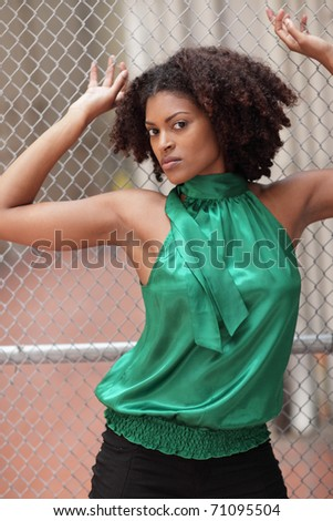 Young model posing by a chainlink fence - stock photo