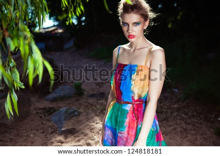 Young model posing in a bright dress on a beach near the deciduous tree - stock photo