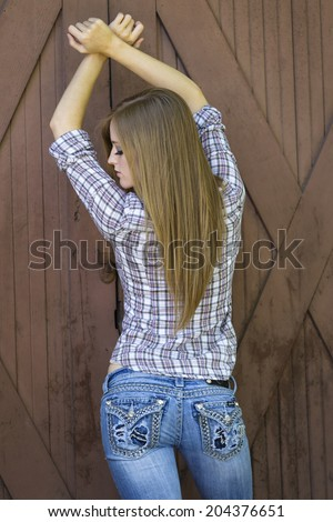 Young model posing in front of a barn in jeans and flannel shirt - stock photo