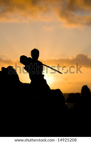 young model posing with a sword in the sunset