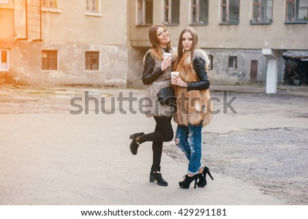 young model walk around town in fur coats in coffee cups - stock photo