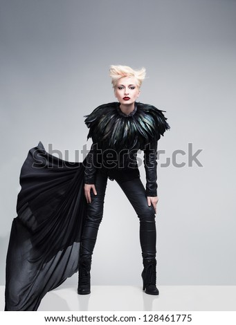 young model wearing leather clothes and feathers posing on  reflective platform - stock photo