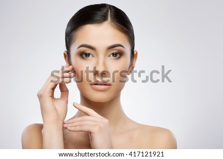 Young model with make-up and ponytail looking at camera. Touching face by one hand. Beauty portrait, head and shoulders, full face. Indoor, studio, gray background - stock photo