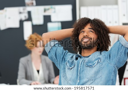 Young modern African American man wearing a blue denim shirt relaxing in his chair at work with a contented smile as he hits upon a new creative idea for a project - stock photo
