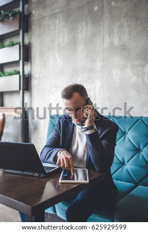 Young, modern and positive business man sitting in cafe and doing his job on notebook, cellphone and tablet.
