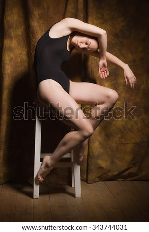 Young modern ballet dancer posing in dark interior - stock photo