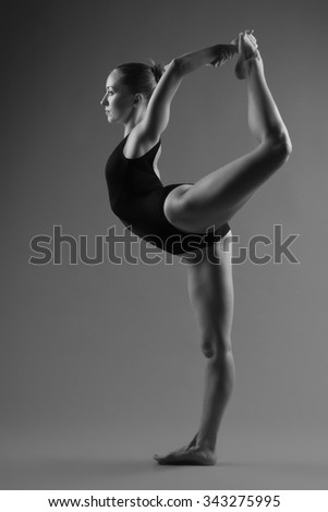 Young modern ballet dancer posing on dark background - stock photo