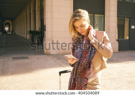 young modern business woman arrived in a European city for a meeting with business partners.portrait of young girl who checks the e-mail outdoors. - stock photo