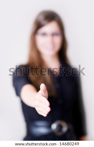 "Young modern business woman reaches her hand out to shake a partner. Shot looks like she has made a ""deal"". Focus on the hand being held out."