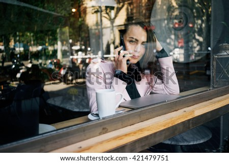 young modern business woman uses a smart-phone for business call while having breakfast in the cafe.beautiful girl talking on the phone while sitting near the panoramic window in the cozy coffeehouse. - stock photo