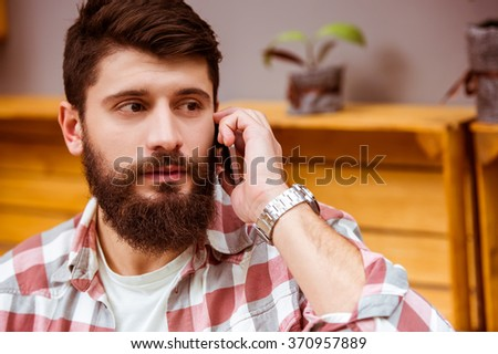 Young modern businessman in casual clothes talking on the phone sitting in a cafe, close-up - stock photo