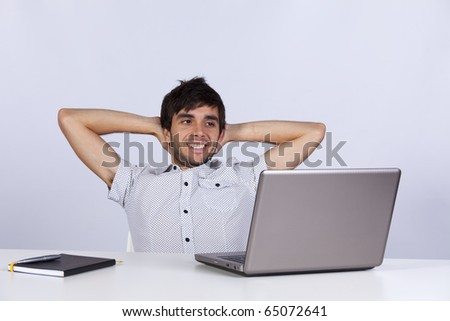 Young modern businessman relaxing at his office happy with his work - stock photo