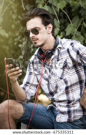 young modern city  man with sunglasses  smartphone and headphones outdoor portrait