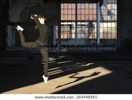 Young modern dancer jumping high in the air in abandoned building. - stock photo
