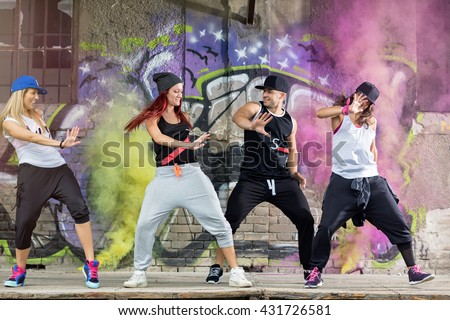 Young modern dancing group practice body jam in front colorful wall - stock photo