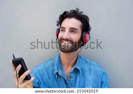 Young modern fashionable man listening to music from mobile phone with headphones - stock photo