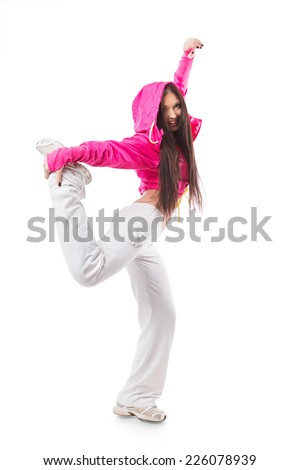 Young modern flexible hip-hop dance girl standing on one leg. Female in white sweatpants and a pink hoodie and sneakers standing on isolated white background. - stock photo
