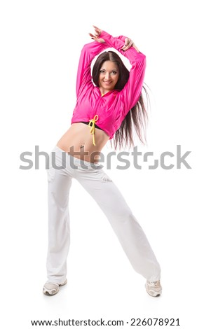 Young modern flexible hip-hop dance girl stretching upwards. Female in white sweatpants and a pink hoodie and sneakers standing on isolated white background. - stock photo