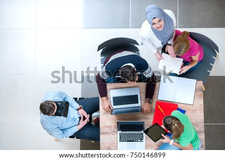 young modern guy and girls are sitting at the school at the table, working together, view from above ,t eamwork cncept