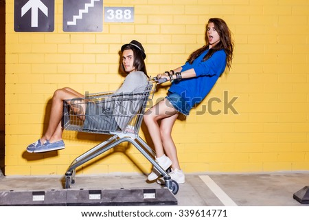Young modern happy couple in love having fun in front of yellow brick wall. Beautiful lady in blue hoodie hold mall trolley with her handsome husband in hat. Both looks to the camera.