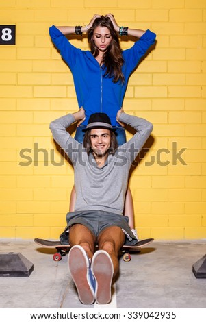 Young modern happy couple in love having fun in front of yellow brick wall. Beautiful longhaired girl in blue hoodie hold her head and looks to her handsome husband in hat. Boy sit on his skateboard. - stock photo