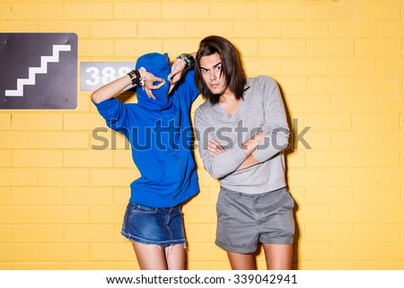 Young modern happy couple in love in front of wall. Beautiful lady in blue hoodie zipped all way up with head making eyes with her hand and her handsome husband with crossed arms looks to the camera. - stock photo