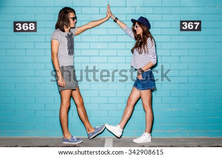 Young modern happy couple in love making frame with their hands and legs in front of a blue brick wall. They are wearing sunglasses and smile to each other. - stock photo