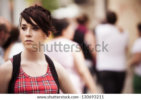 Young modern looking girl over urban background - stock photo