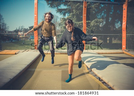 young modern stylish couple urban city jumping trampoline outdoors - stock photo