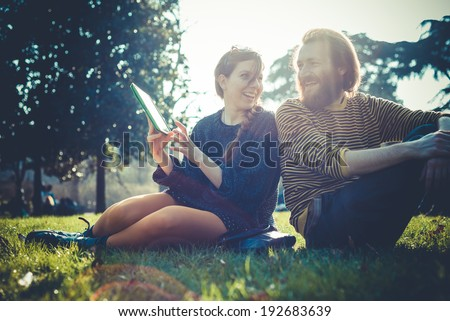 young modern stylish couple using tablet in urban city outdoors - stock photo