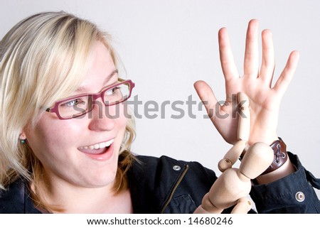 Young modern woman giving a high-five to a wooden stick man toy. She looks as if she has scored a deal or goal. - stock photo