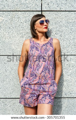 Young modern woman in sunglasses by the wall in city smiling. - stock photo