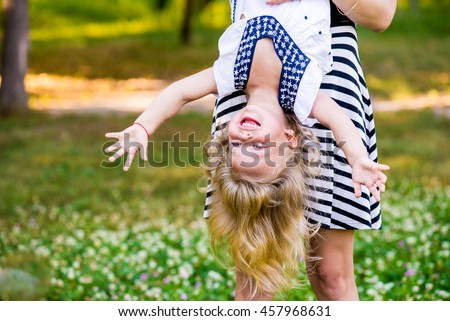 Young mom and cheerful adorable blond tot girl playing, having fun together in park in summertime, mother playfully holding her cute little daughter upside down, close up - stock photo
