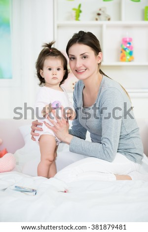 Young mom and her baby girl looking at camera on the bed in baby room.Shallow doff