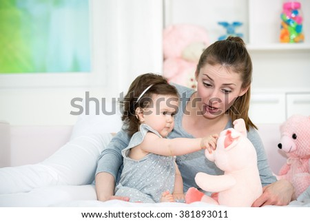 Young mom and her baby girl playing with a baby toys in the bed. Shallow doff - stock photo