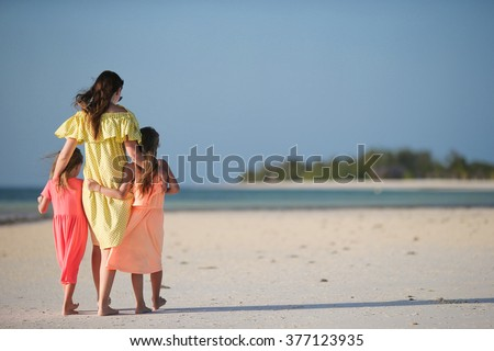 Young mom and little girls during summer beach vacation