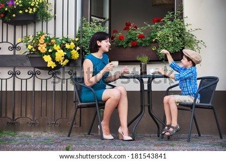 Young mom having coffee with her son - stock photo