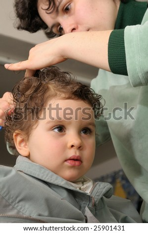 Young mom is cutting hair of her 2 year old daughter at home. - stock photo