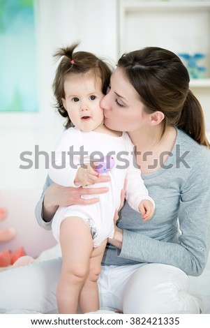 Young mom kissing her baby girl on the bed.Baby standing and looking at camera with open mouth .Shallow doff - stock photo