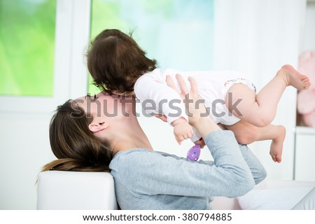 Young mom lying on back and kissing her baby little girl. Shallow doff - stock photo