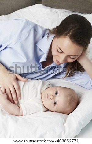 Young mom on bed with baby son