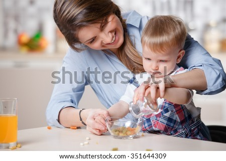 young mom playing with her little toddler son at home