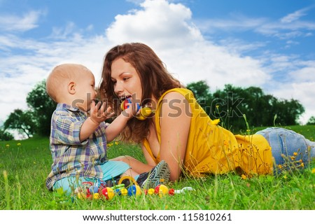 young mom playing with her son in the park - stock photo
