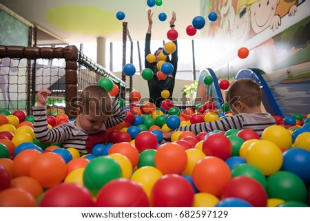 Young mom plays with her kids at pool with colorful balls in a children's playroom