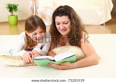 Young mom reads a book for child on a floor