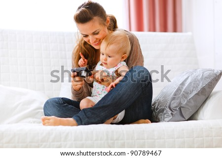 Young mom showing her interested baby photos on camera - stock photo