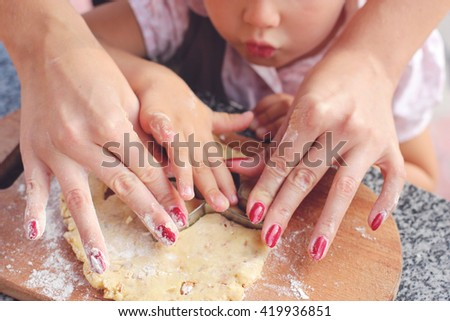 Young mom teaching a little kid to make cookies in the kitchen/family baking together - stock photo